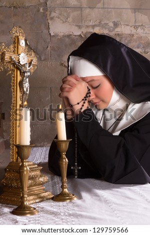 Closeup of an altar of a medieval 17th century church and a young nun in prayer - stock photo
