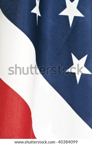 Closeup of an American flag showing the red, white and blue with some of the stars.