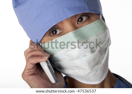 Closeup of an Asian female medical professional wearing scrubs and a mask while talking on a cell phone. Horizontal shot. Isolated on white. - stock photo