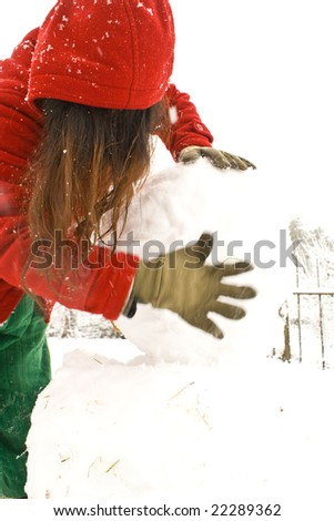 Closeup of an asian lady in colorful clothes makes a snowman in the garden.