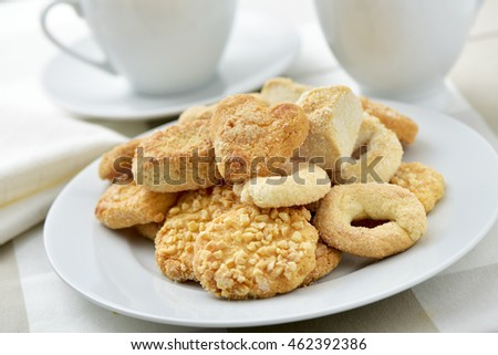 closeup of an assortment of different shortbread biscuits in a white plate, on a set table with some cups of tea or coffee
