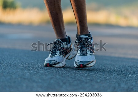 Closeup of an athlete runner's feet and shoes running along a road outdoors with a mountain background. Men fitness during sunrise jogging - stock photo
