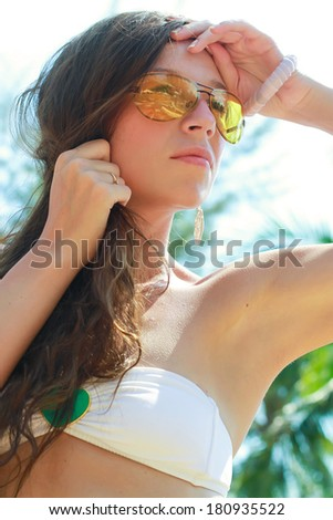 Closeup of an attractive young woman in sunglasses on the beach - stock photo
