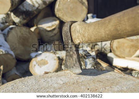 Closeup of an axe sticking in a chunk of firewood in front of a staple of firewood.
