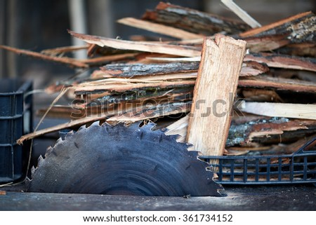 Closeup of an electric saw and a pile of chopped wood near it