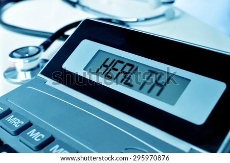 closeup of an electronic calculator with the word health in its display and a stethoscope, depicting the concept of the healthcare business - stock photo