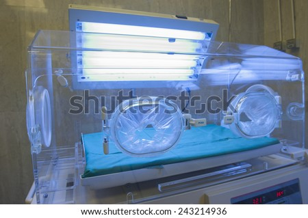 Closeup of an infant incubator technology in a medical center hospital - stock photo