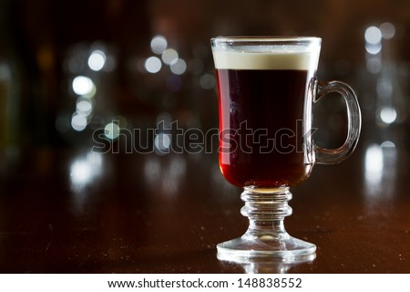 closeup of an irish coffee saved on a dark bar with a float of heavy cream - stock photo