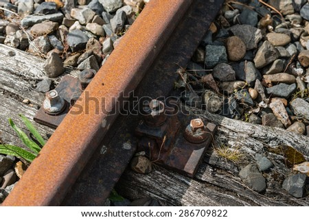 Closeup of an old and rusty section of railroad tracks with sleepers and gravel. - stock photo