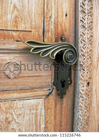 closeup of an old  carved wooden door with doorknob - stock photo