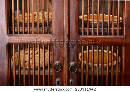 Closeup of an old fashioned pie safe with pumpkin and apple pies behind the doors. Four fresh baked holiday pies on two shelves of the wooden cooling cabinet. Horizontal filling the frame. - stock photo