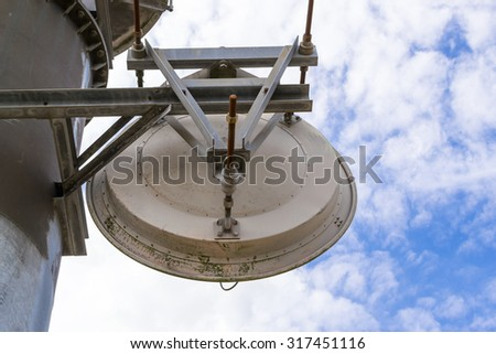 Closeup of an old military satellite with a blue sky and white clouds