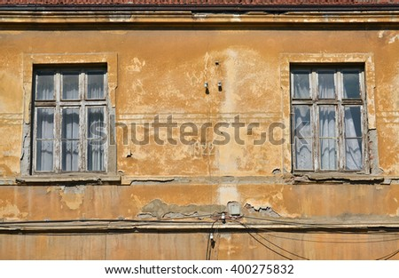 Closeup of an old yellow facade and two windows with curtains - stock photo