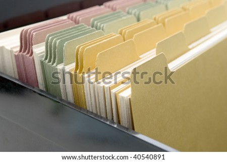 Closeup of an opened box of index cards.  Black box, white cards with dividers coloured pink, green and yellow.