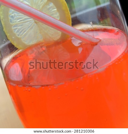 Closeup of an orange-colored beverage with a lemon slice and a drinking straw with an outdoor scenery in background, referring to concepts such as cocktails, summertime, refreshment, and relaxation - stock photo