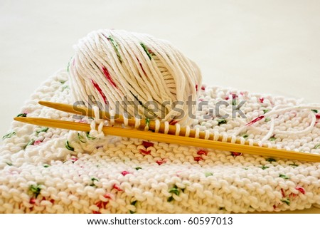 Closeup  of an unfinished knitting project with wooden needles and worsted weight cotton yarn. - stock photo