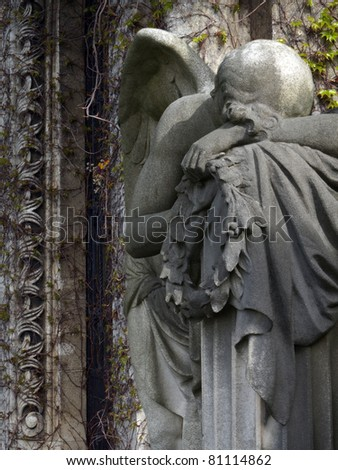 closeup of angel over wall overgrown whit vine - stock photo