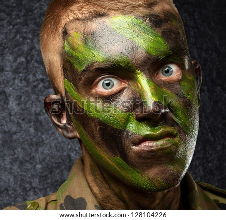 closeup of angry soldier with painting against a grunge background - stock photo