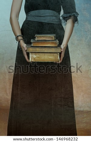 closeup of antique torn books with a hands of a young woman held against black dress on a grunge textured background  - stock photo