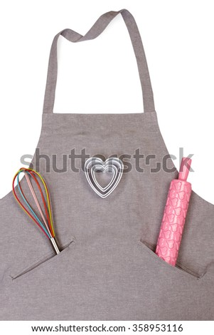 Closeup of apron with pink rolling pin, whisk and plastic heart-shaped cutters isolated on white background - stock photo
