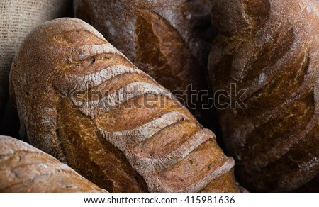 Closeup of artisan french breads. French baguettes, crispy looking, whole weat bread in rustic basket
