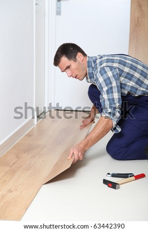Closeup of artisan installing flooring in room - stock photo