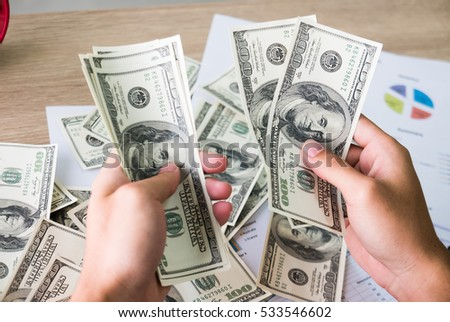 Closeup of Asian male hands counting bunch of dollars banknotes with business charts background for business, finance, tax and people concept