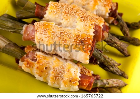 Closeup of asparagus rolls with prosciutto and puff pastry, decorated with sesame seeds.