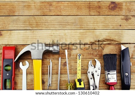 Closeup of assorted work tools on wood - stock photo