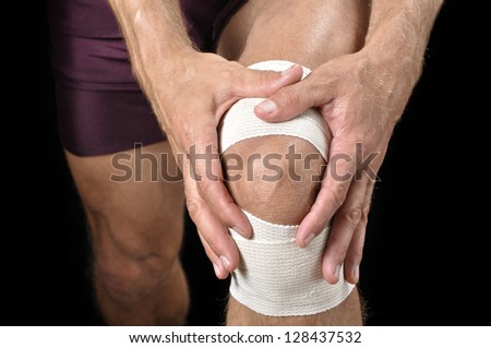 Closeup of athletic man tending wrapped injured knee on black background - stock photo