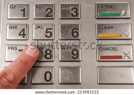 Closeup of atm machine with a finger pressing metallic keyboard - stock photo