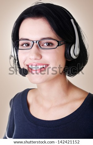 Closeup of attractive customer support representative smiling with headset on brown background - stock photo