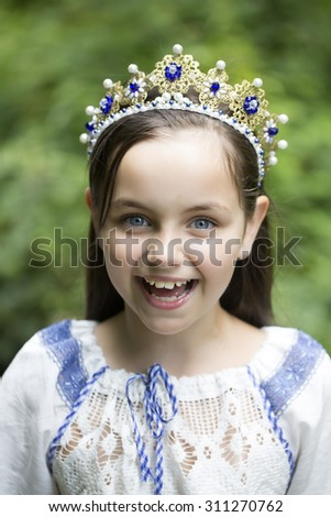 Closeup of attractive smiling princess girl with long brunette hair in traditional ukrainian embroidery white blue colors and beautiful diadem with diamonds in gold outdoor, vertical picture - stock photo