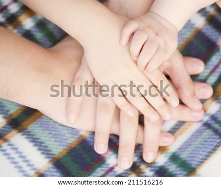 Closeup of baby, child, mother, father hands. Selective focus on infant hand. Unity, support, protection and happiness. Family concept - stock photo
