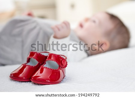 Closeup of baby red patent leather shoes over a bed and adorable babe lying on the background - stock photo