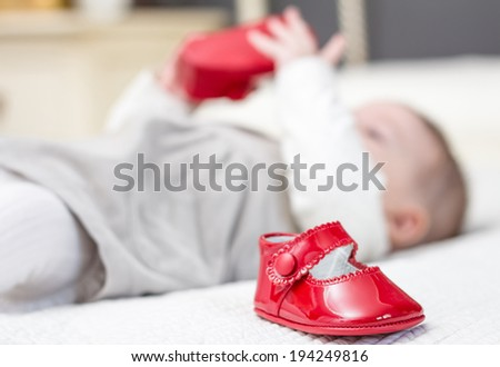 Closeup of baby red patent leather shoes over a bed and adorable babe playing on the background - stock photo