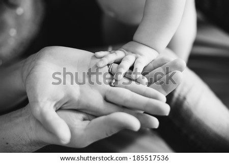 Closeup of baby's and parent's hands. black and white picture - stock photo
