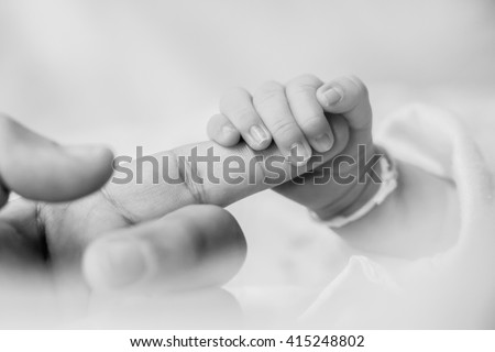 closeup of baby's hand gripping adult's finger, black and white - stock photo