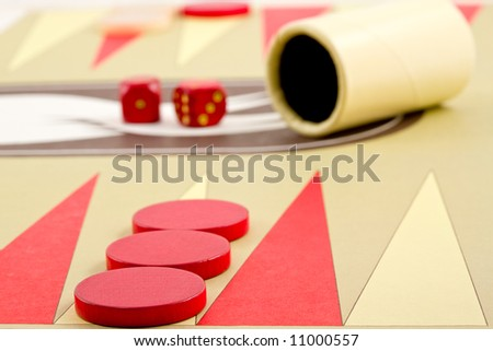 Closeup of Backgammon Board with Pieces, Dice, and Cup - stock photo