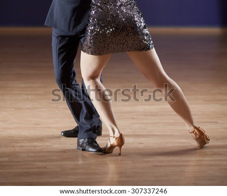 closeup of ballroom dancer's legs as they dance a tango - stock photo