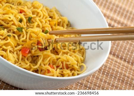 closeup of bamboo chopsticks holding vegetarian noodles - stock photo