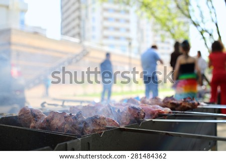 Closeup of barbecue with slices of meat on skewers in front of people - stock photo