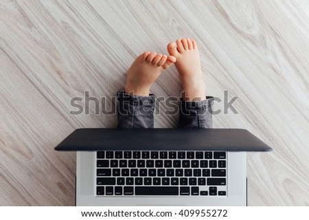 Closeup of barefoot little girl with big laptop on the floor - stock photo