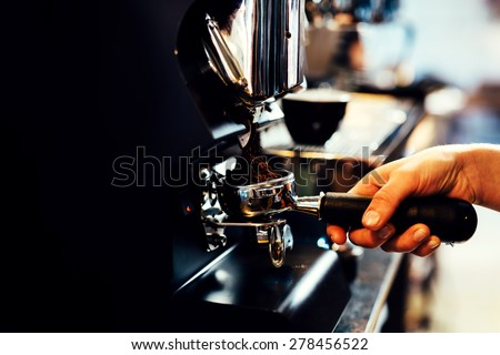 Closeup of barista grinding coffee - stock photo