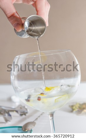 Closeup of barman hand pouring alcoholic drink with a jigger on glass to prepare gin tonic cocktail - stock photo