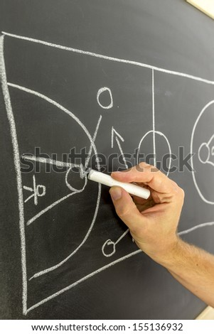 Closeup of basketball coach drawing game strategy on black board. - stock photo