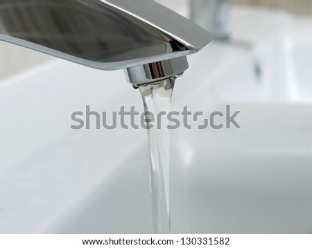 Closeup of bathroom chrome faucet with running water - stock photo