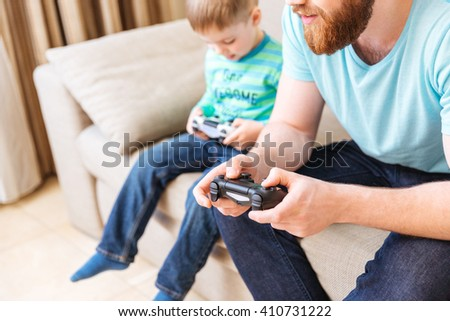 Closeup of bearded man sitting on sofa and playing computer games with his little son