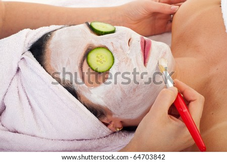 Closeup of beautician applying facial mask and cucumber slices to a woman in a spa salon