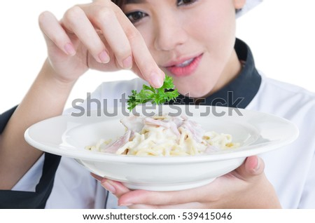 Closeup of beautiful Asian woman chef in restaurant cooking and garnish spaghetti dish with green parsley isolated on white background